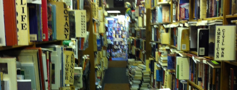 A photo of overstuffed bookshelves in a used bookstore.